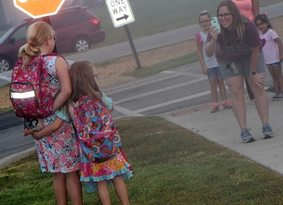 Keri Coots takes a photo of her daughters, Lily, a fifth-grader, and Charlotte, a first-grader, as they start their first day of school at CES.