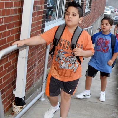 CES fourth-grader Nicholas Almeida, at left, and his brother, second-grader Matheus Almeida, walk in for the first day of school.