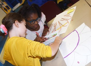 CMS sixth-graders Destiny Abell, at left, and Maliyah Harris add color to their artwork, inspired by Georgia O'Keeffe's work.