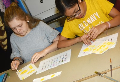 CMS eighth-graders Alexis Sharp, at left, and Angelica Seng try new painting techniques.