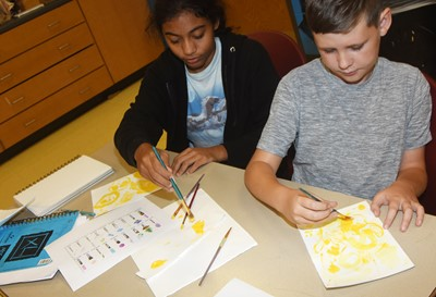 CMS seventh-grader Falicity Lewis, at left, and iEagle fifth-grader Ryan Tungate try new painting techniques.
