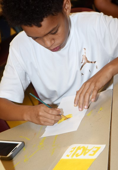 CMS sixth-grader Anthony Goins tries a new painting technique.
