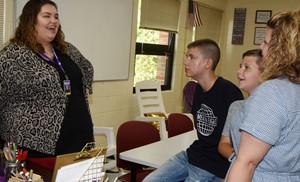 CHS teacher Morgan Dalton talks with freshman Blake Tungate, at left, his brother Ryan, a fifth-grade iEagle student, and their mother Rebecca.