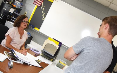 CHS teacher Mary Jo Hazel talks with junior Arren Hash and his father Garin.