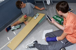 CMS seventh-graders Taylan Hunt, at left, and Jaxon Garrett release their car as they calculate its speed.