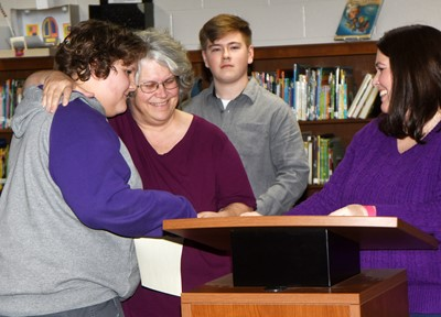 CMS art teacher Jo Ann Harris hugs her son, Zeke, a seventh-grader, as he is inducted as a charter member of the CMS National Junior Art Honor Society.