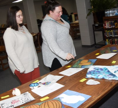 CMS eighth-grader Brianna Dobson looks at her artwork with her mother, Rachael.