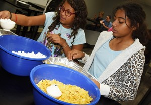 CMS sixth-grader Brianna Mitchell, at left, and seventh-grader Falicity Lewis measure ingredients to make rice krispie treats.