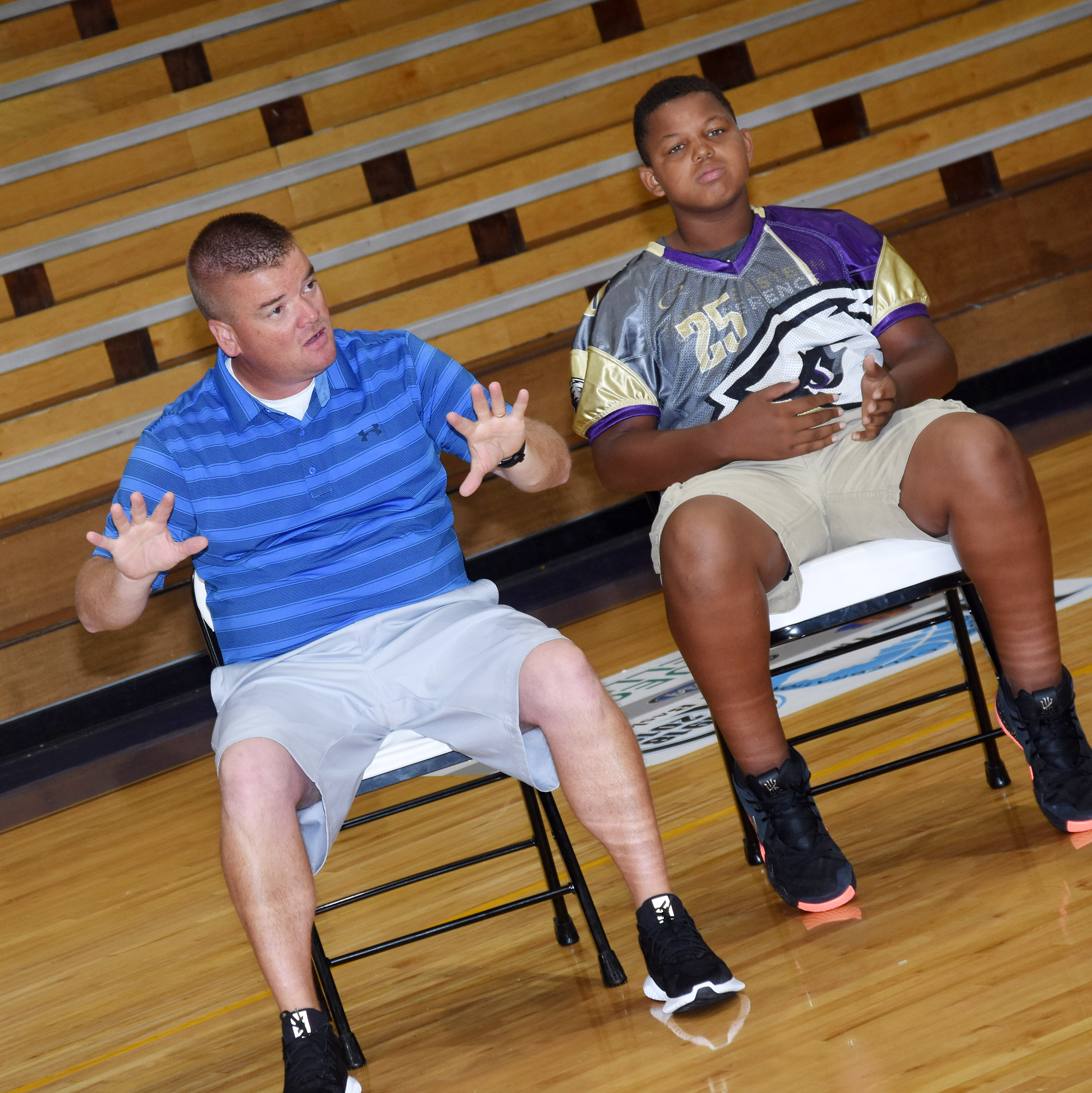CMS physical education teacher Dale Estes talks to his students about the expectations for his class. At right is eighth-grader Keondre Weathers.