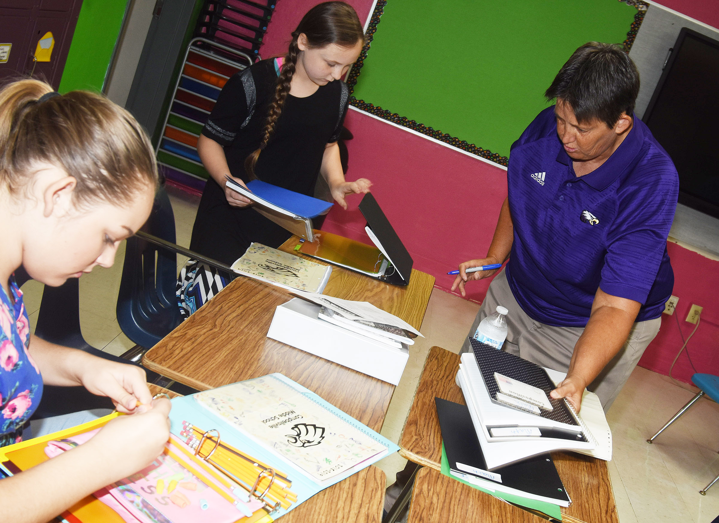 CMS exceptional child educator Katie Campbell helps sixth-graders Piper Maggard, at left, and Shyanna Young prepare their school supplies.