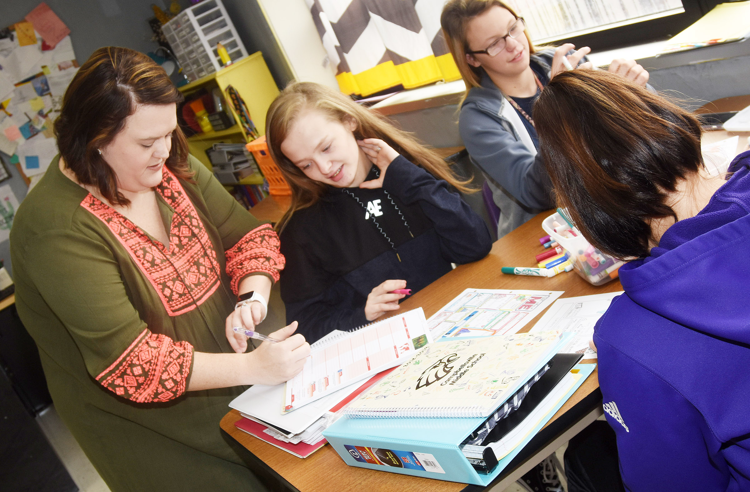 CMS eighth-grade teacher Paige Cook talks to her students. Pictured are eighth-graders Davanna Reardon, center, and Jade Wheeler.