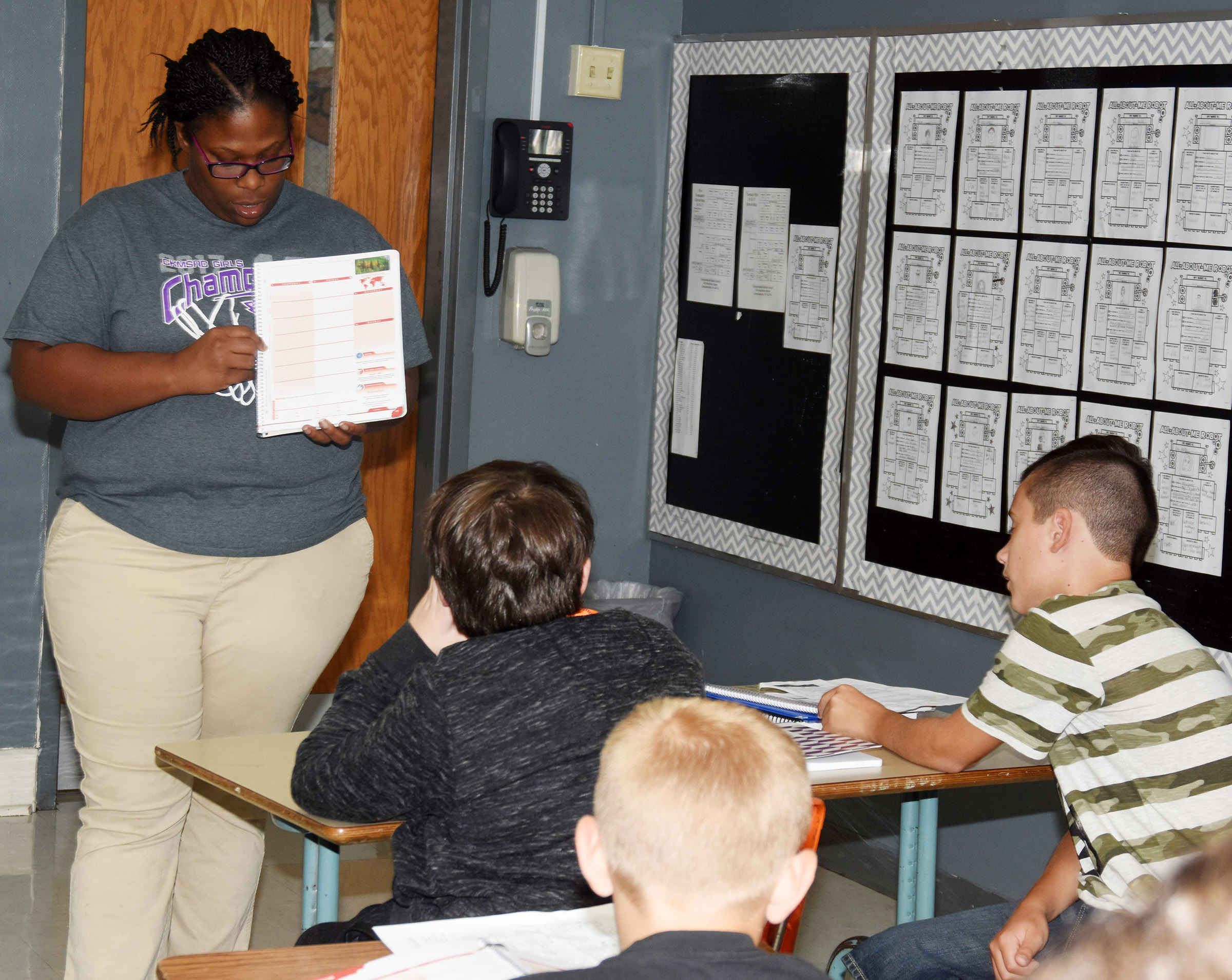 CMS sixth-grade teacher Tiarra Cecil talks to students about their academic planners.