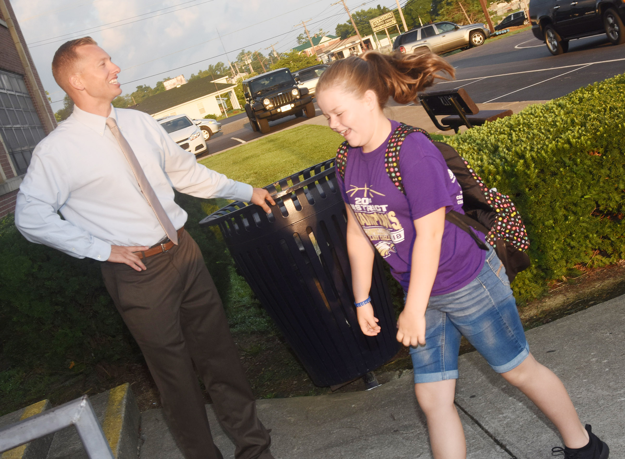CMS Principal Zach Lewis greets sixth-grader Miley Hash as the start of the day.