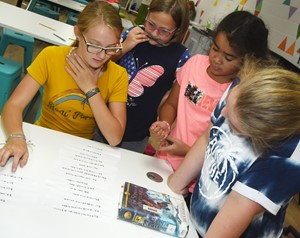 From left, iEagle seventh-grader Lilyan Murphy, fourth-grader Addelyn Dooley, fifth-grader Sophia Santos and sixth-grader Kiera Bailey work together to decide what entertainment they will pay for each month.