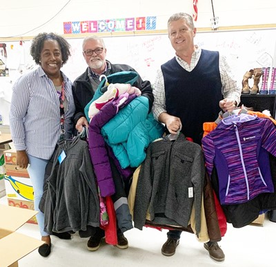 Campbellsville Middle and High School Youth Services Center Coordinator Theresa Young receives winter coats, hats and gloves from Campbellsville Apparel Co., represented by George Wise, center, and Chris Reynolds.