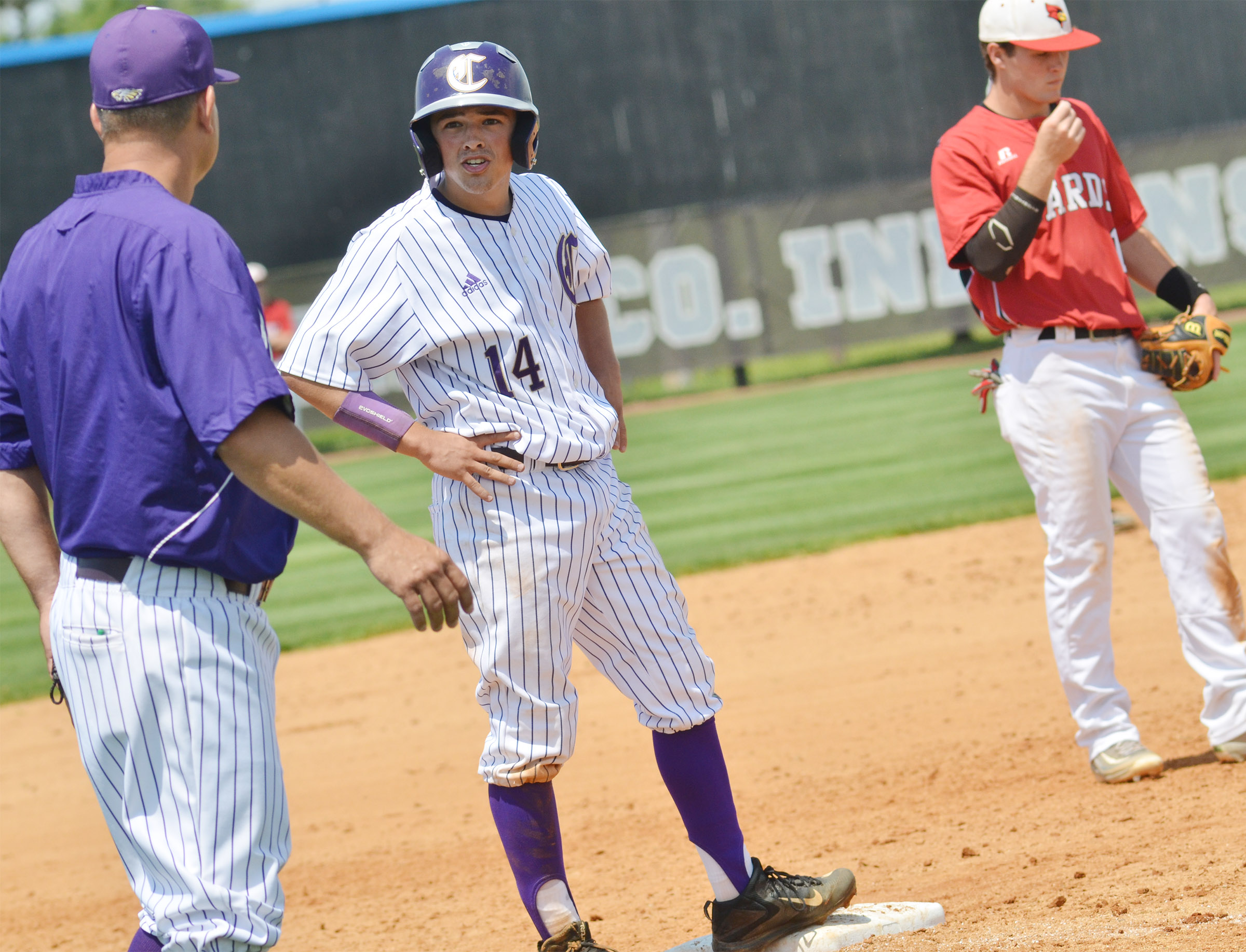 CHS sophomore Ryan Kearney talks to head baseball coach Kirby Smith as he reaches third base.
