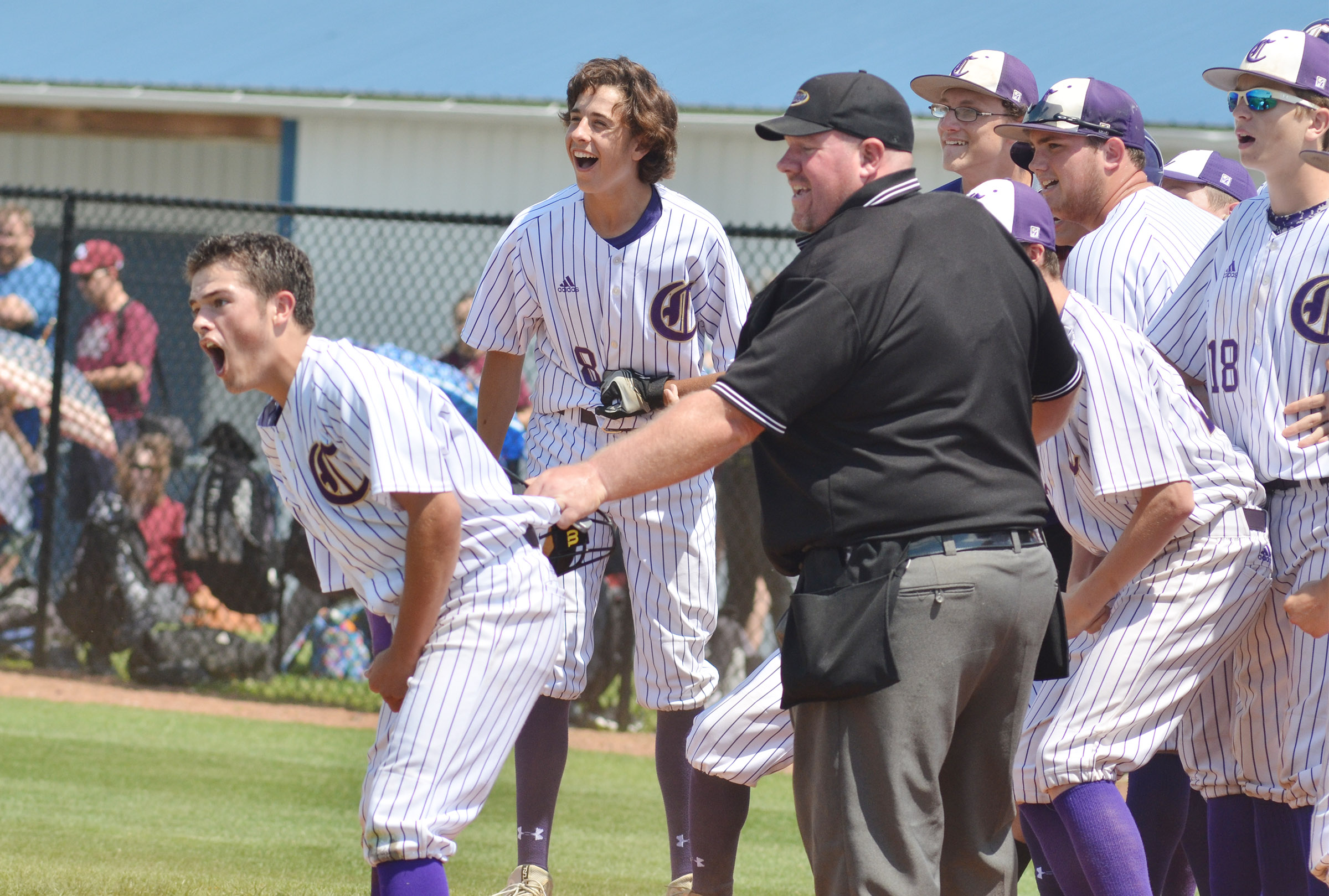CHS baseball players greet sophomore Treyce Mattingly as he scores after hitting a three-run homerun.