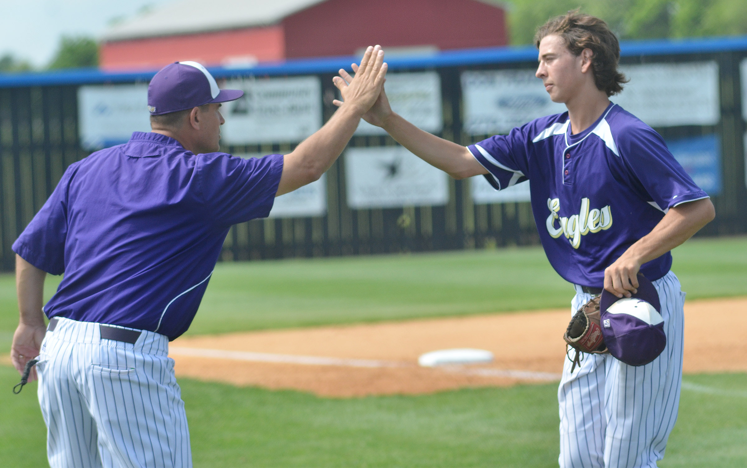 CHS head baseball coach Kirby Smith high fives Campbellsville Middle School eighth-grader John Orberson after an inning.