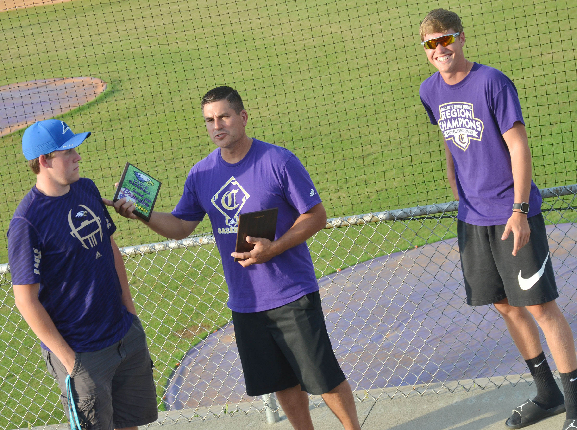 CHS head baseball coach Kirby Smith honors seniors Jared Brewster, at left, and Zack Bottoms for their dedication to their team.