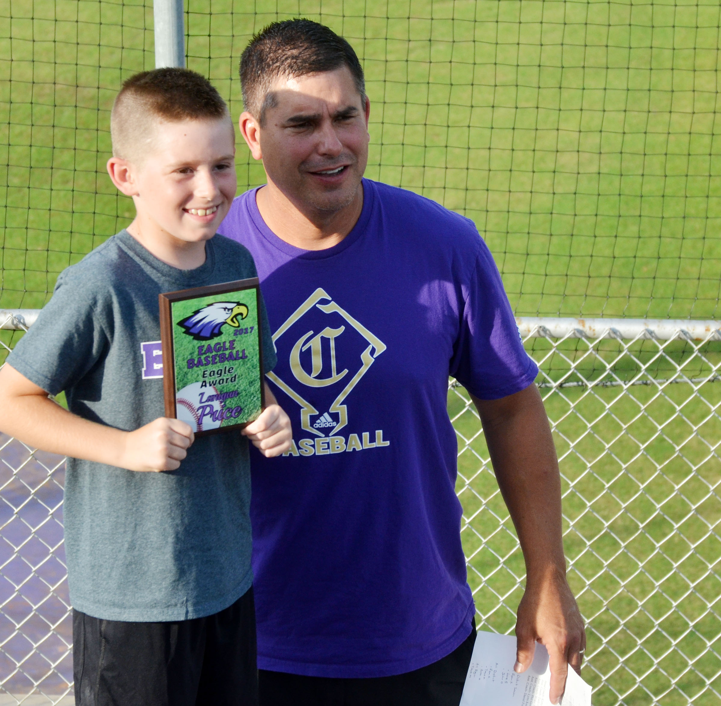 CHS head baseball coach Kirby Smith honors Campbellsville Elementary School second-grader Lanigan Price with an Eagle Award for being the team's bat boy.