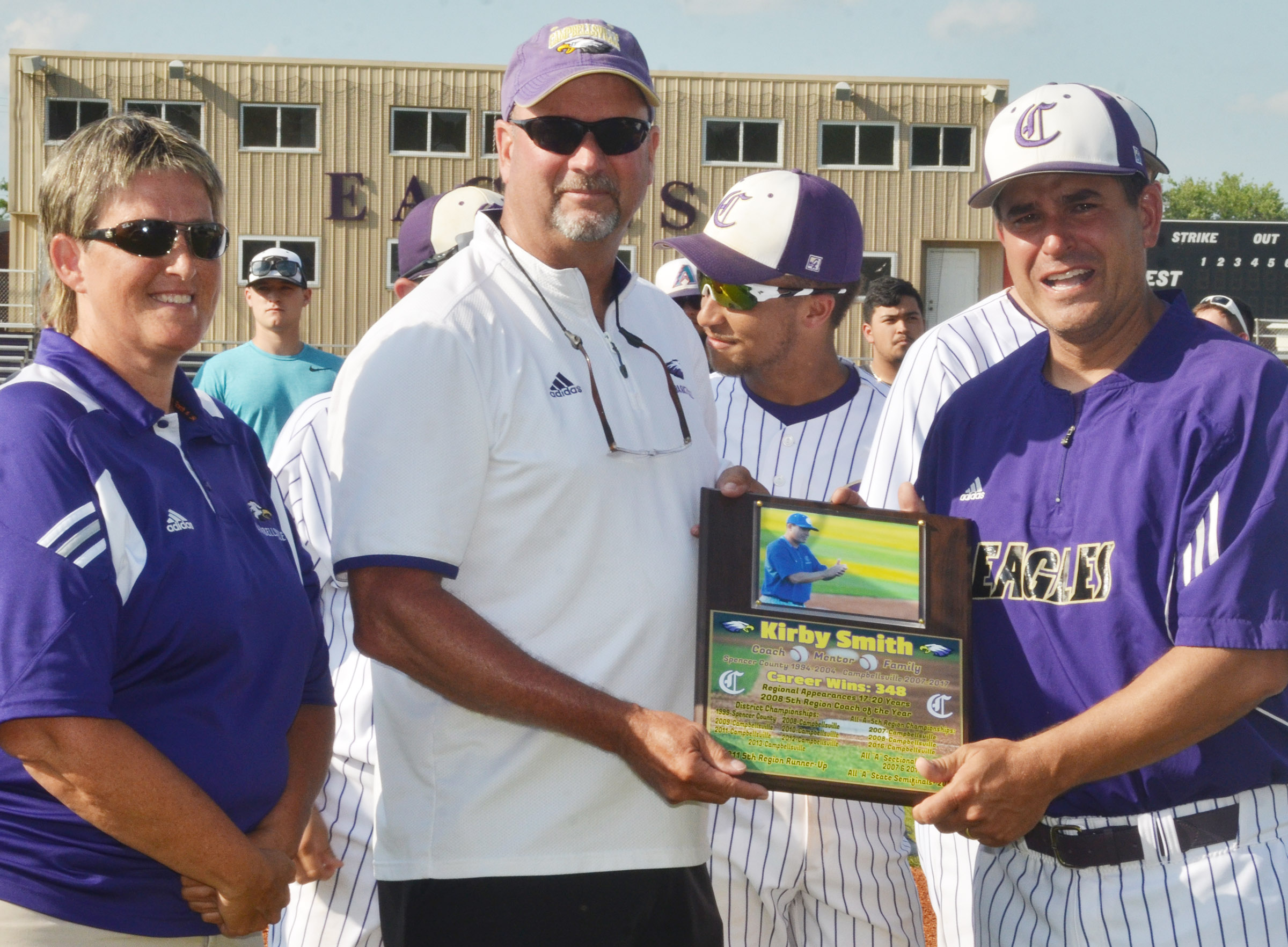 CHS head baseball coach Kirby Smith is honored for completing his 11th season leading the Eagles. Athletic Director Tim Davis, center, and Assistant Athletic Director Katie Wilkerson presented him with a plaque and many of his former players surprised him by attending the ceremony.