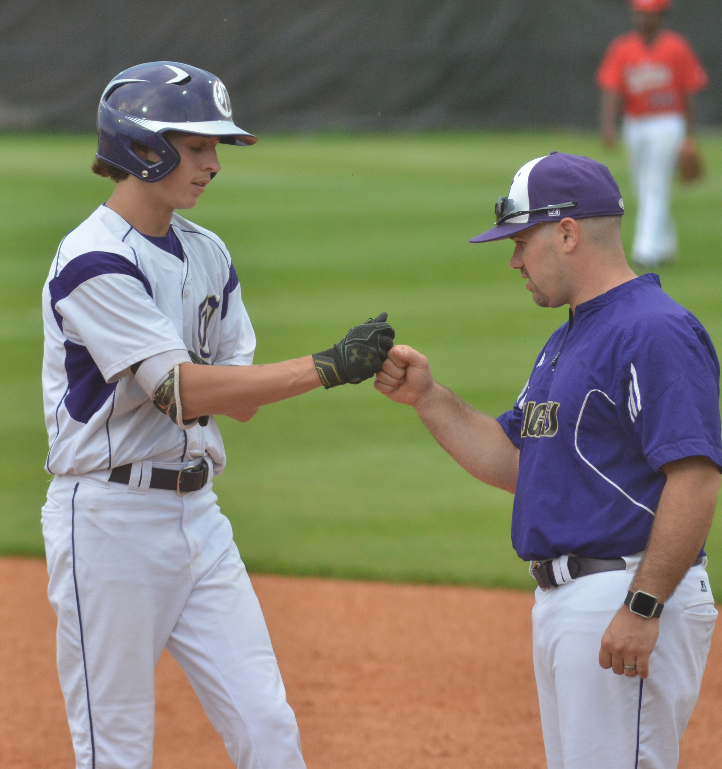 Campbellsville Middle School eighth-grader John Orberson bumps fists with assistant coach Blake Milby after getting a hit.