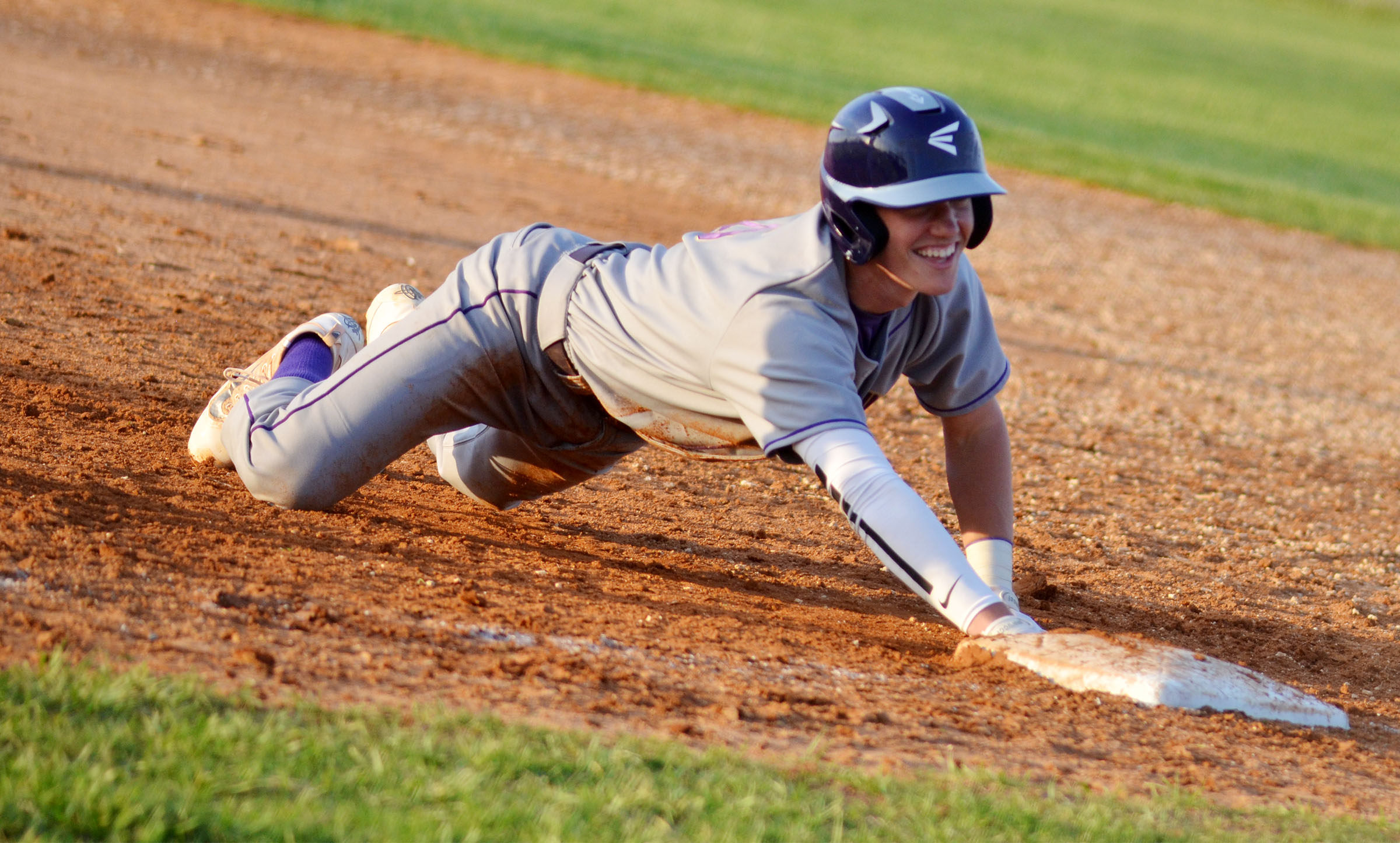 CHS senior Zack Bottoms smiles as he dives back to first base.