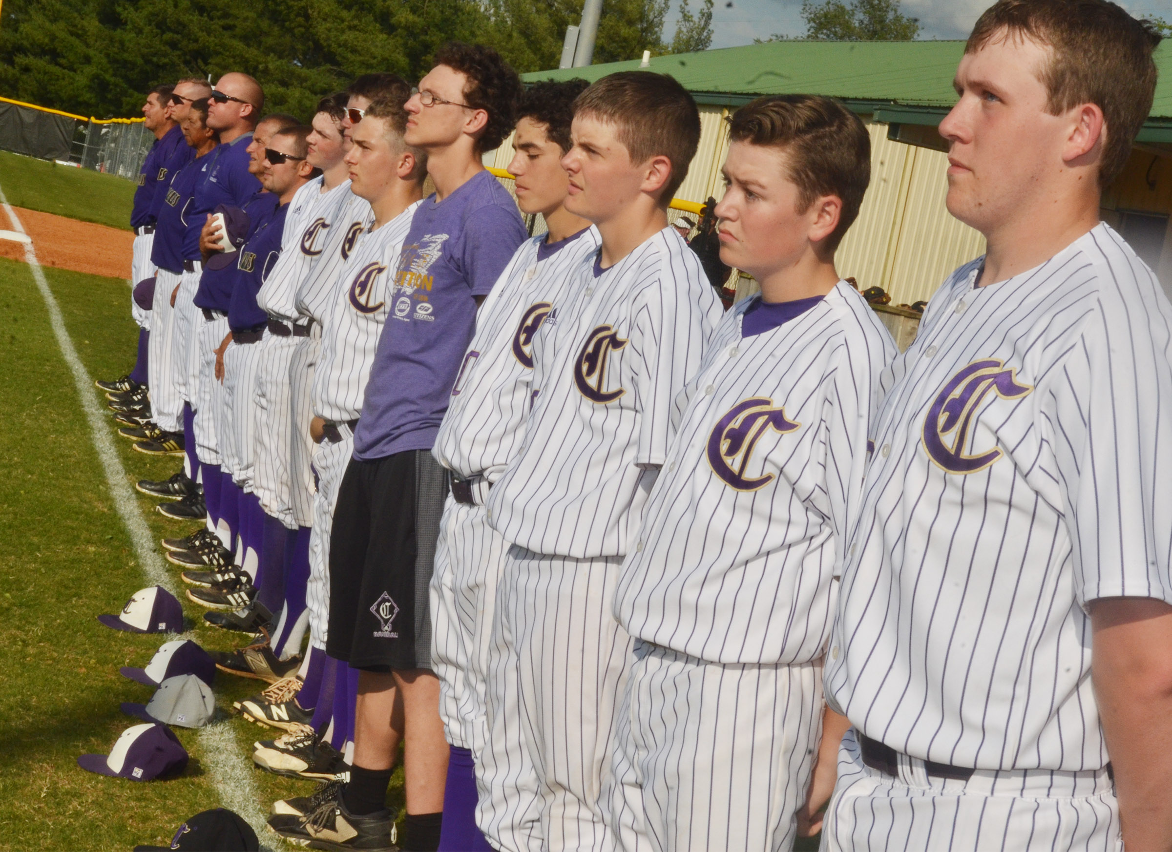 CHS baseball players and coaches stand for the National Anthem.