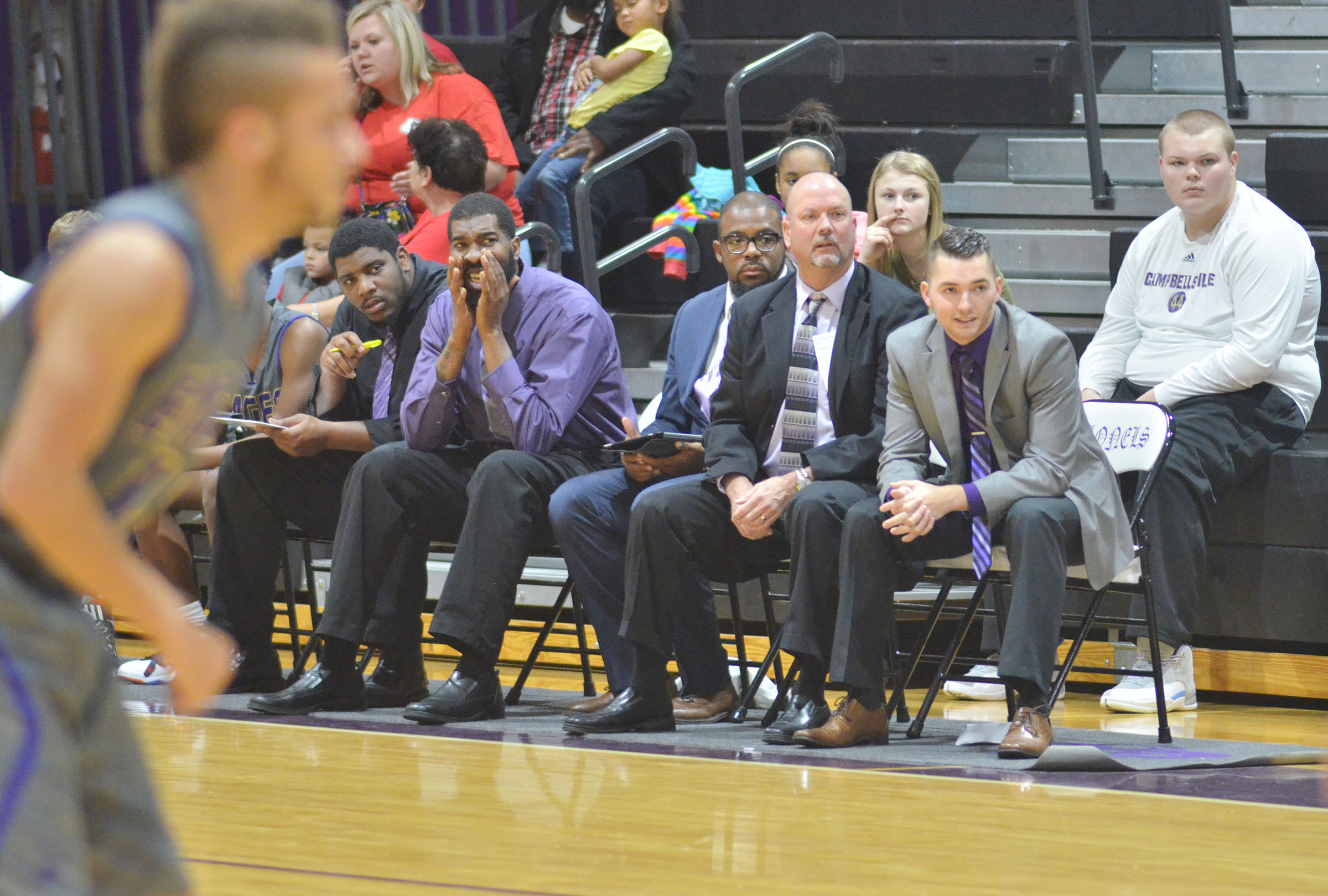 CHS boys' basketball coaches watch from the sidelines.