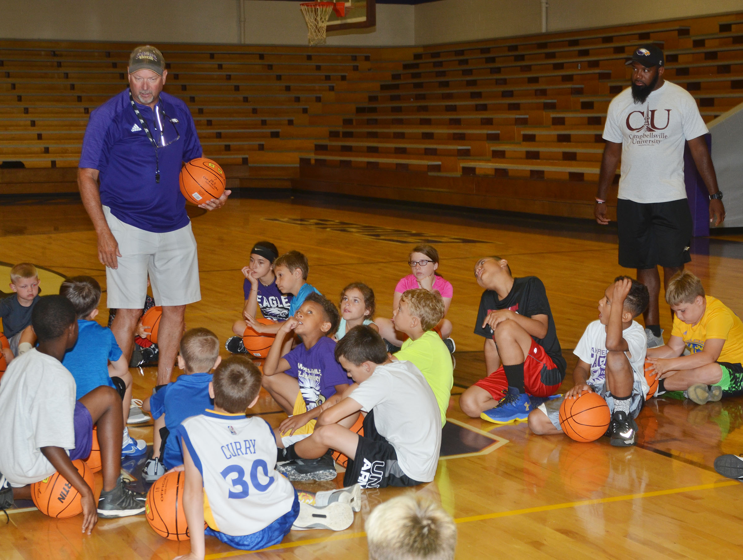 CHS boys' head basketball coach Tim Davis talks to campers.