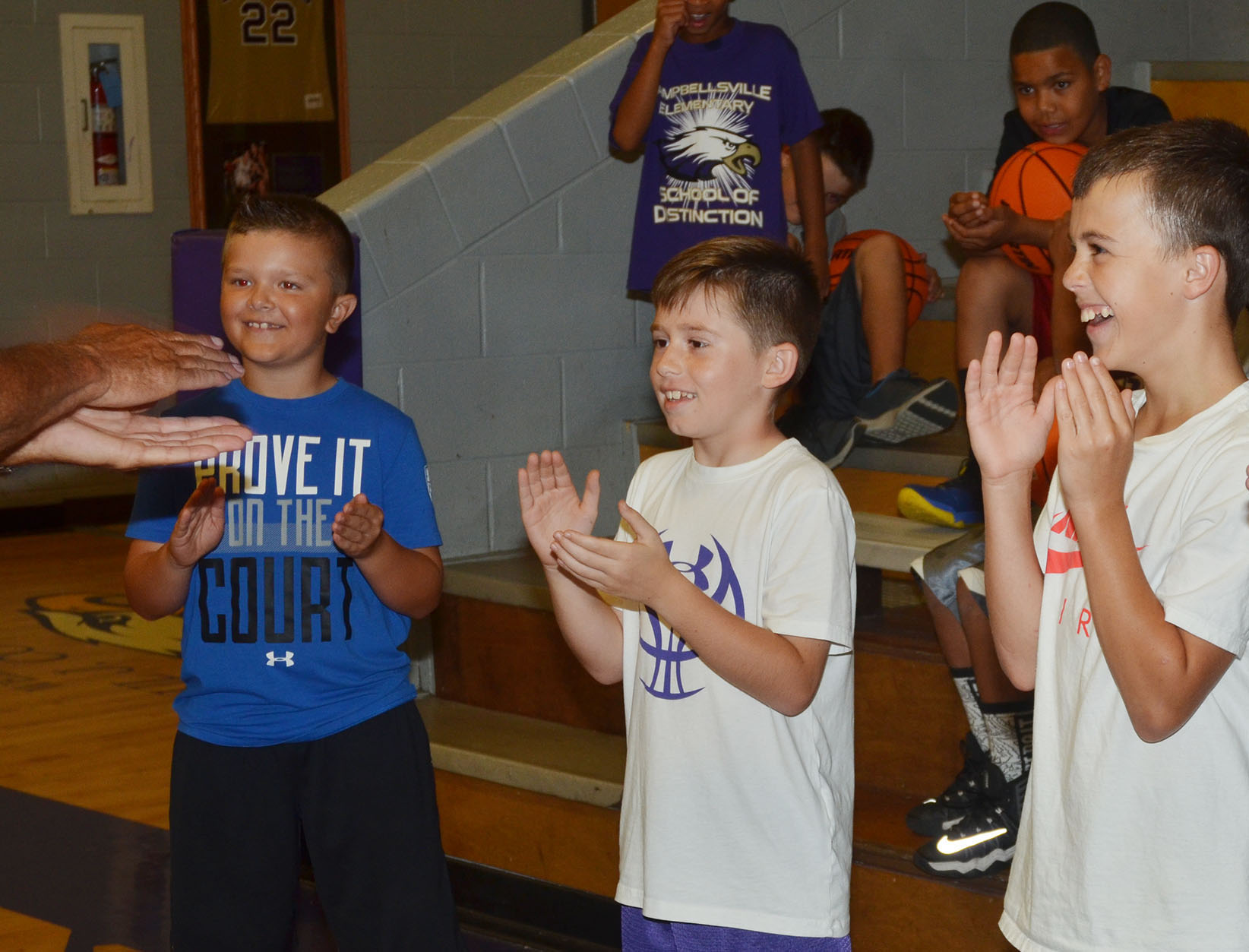 From left, campers Cayton Lawhorn, Lanigan Price and Chase Hord play a hand-eye coordination with CHS boys' head basketball coach Tim Davis.
