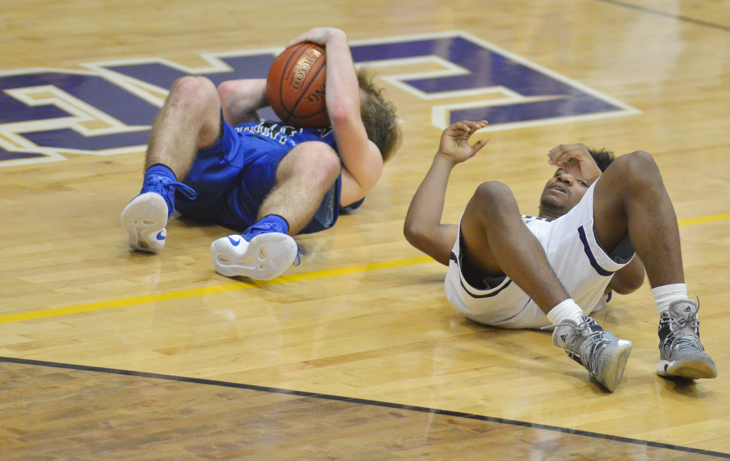 CHS junior Tyrion Taylor lands on the floor after battling with a Clinton County defender for the ball.