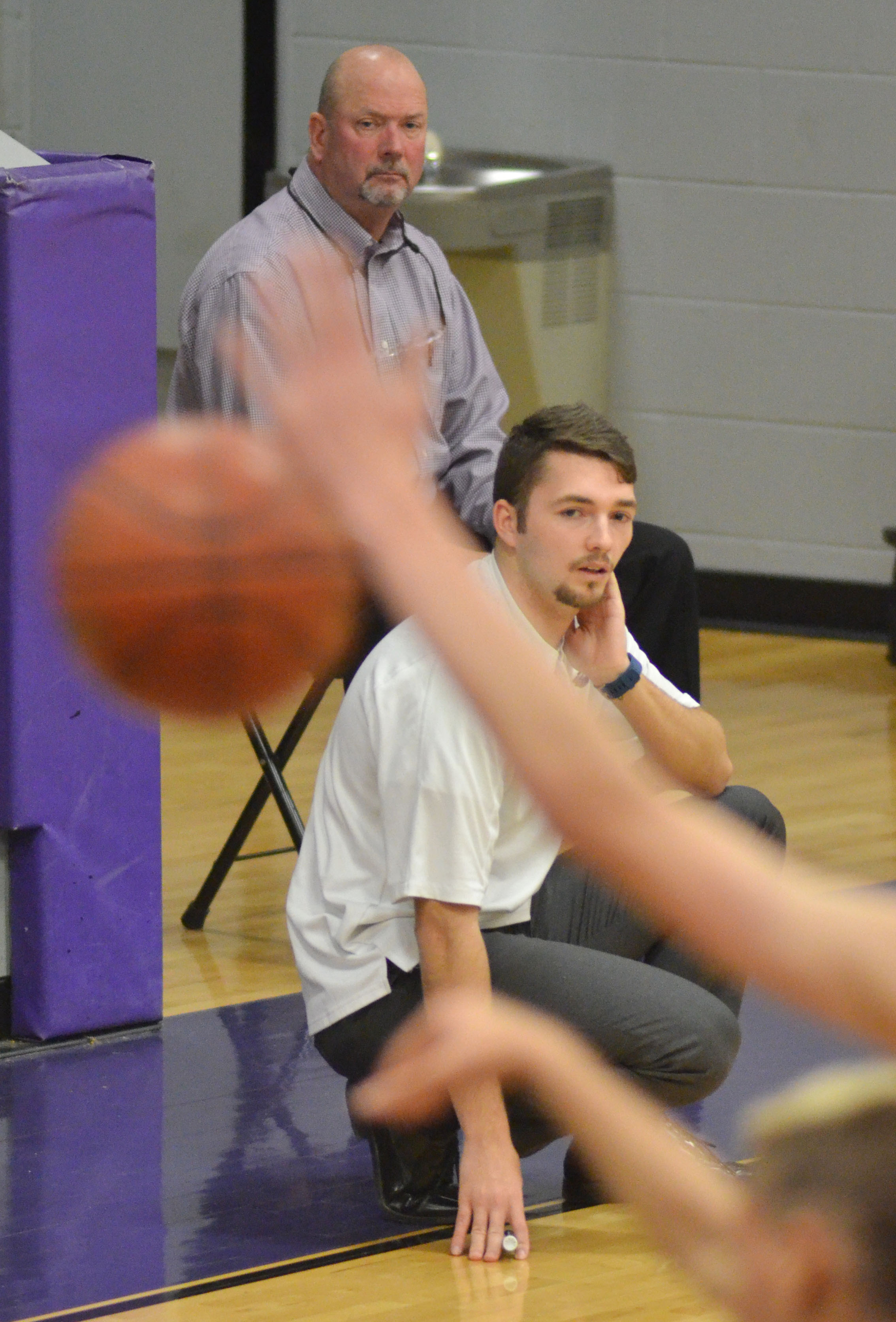 CHS boys' head basketball coach Tim Davis, in back, and Cody Wills watch as the JV team plays.