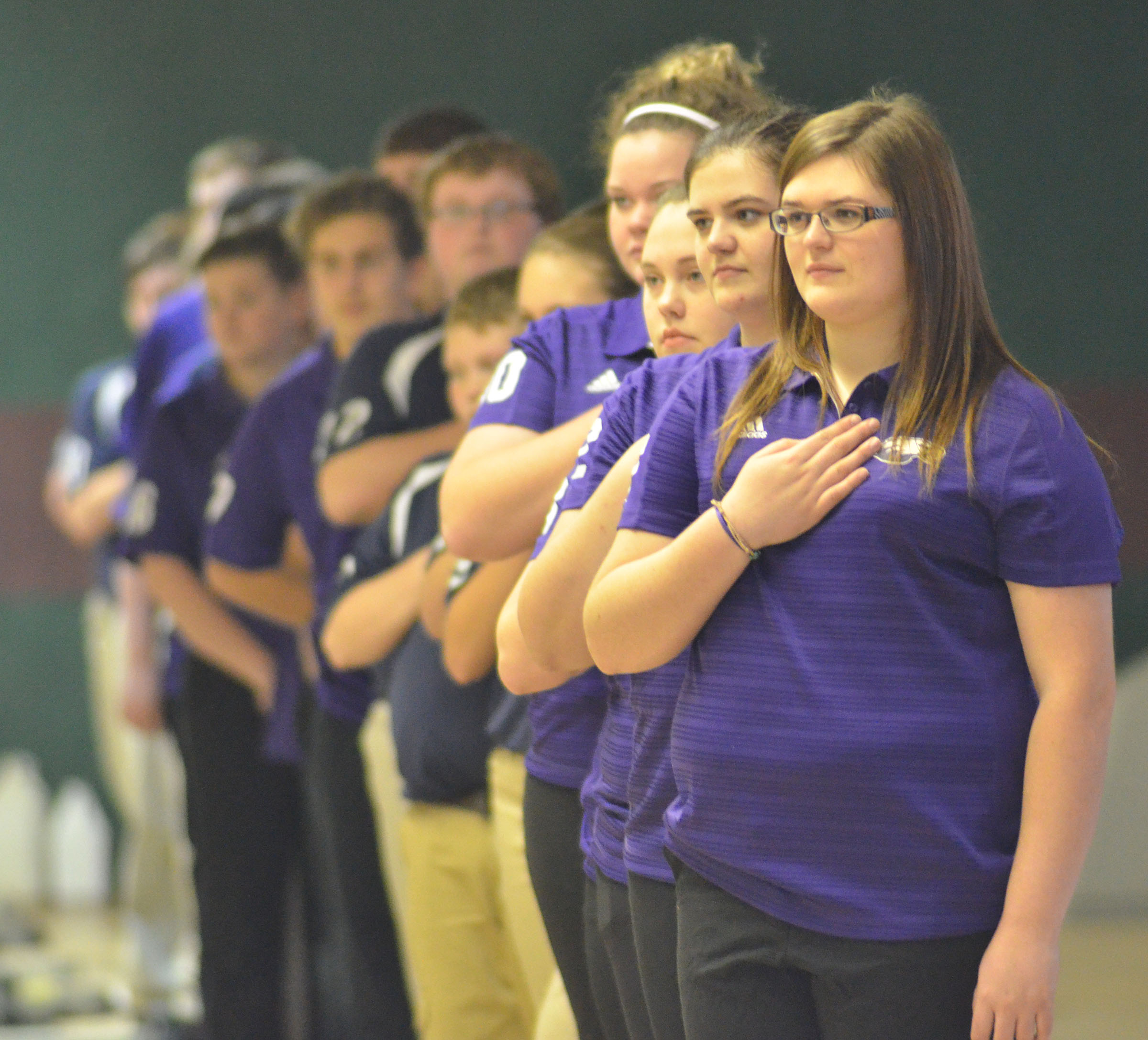 CHS bowling team members, led by senior Vera Brown, stand as the National Anthem plays.