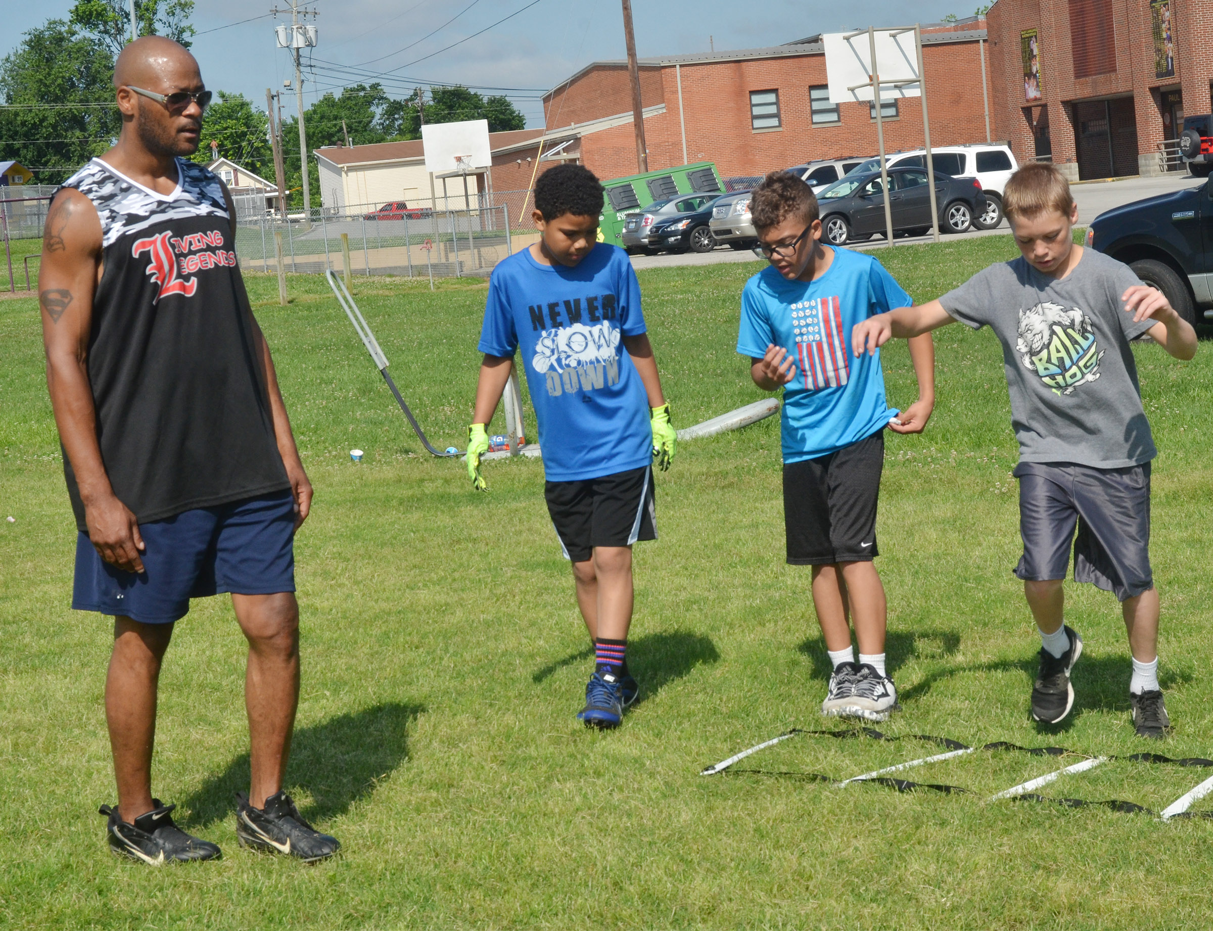 Former NFL player Tony Driver helps, from left, Tashaun Hart, Logan Phillips and Tuff Harper with their footwork.