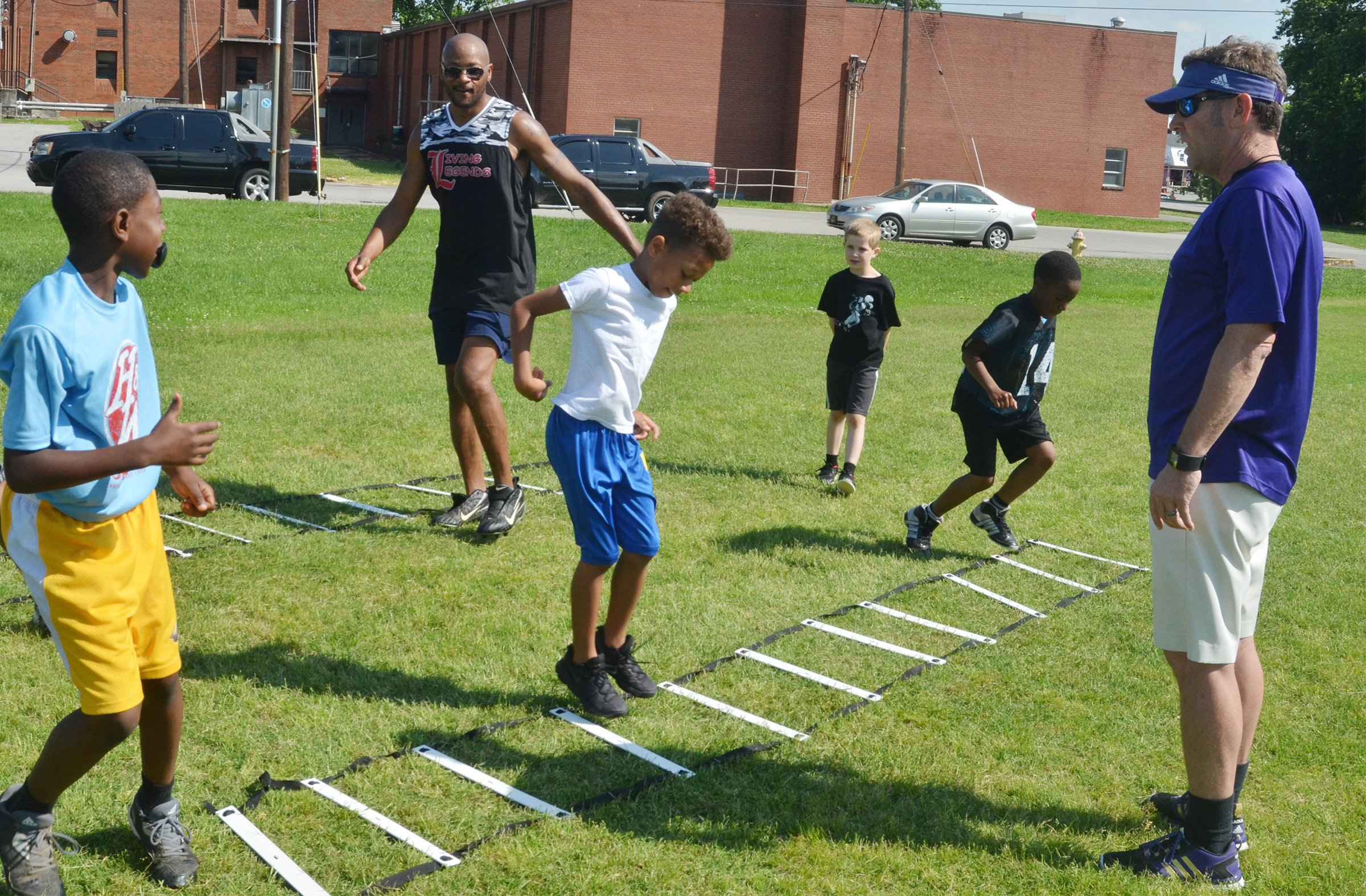Former NFL player Tony Driver, at left, and assistant coach Herb Wiseman work with campers on a drill.