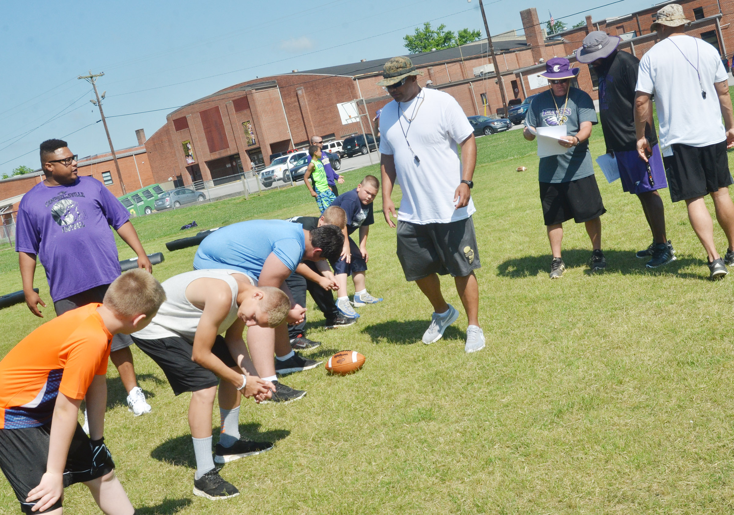 CHS assistant football coaches work with campers on fundamentals.