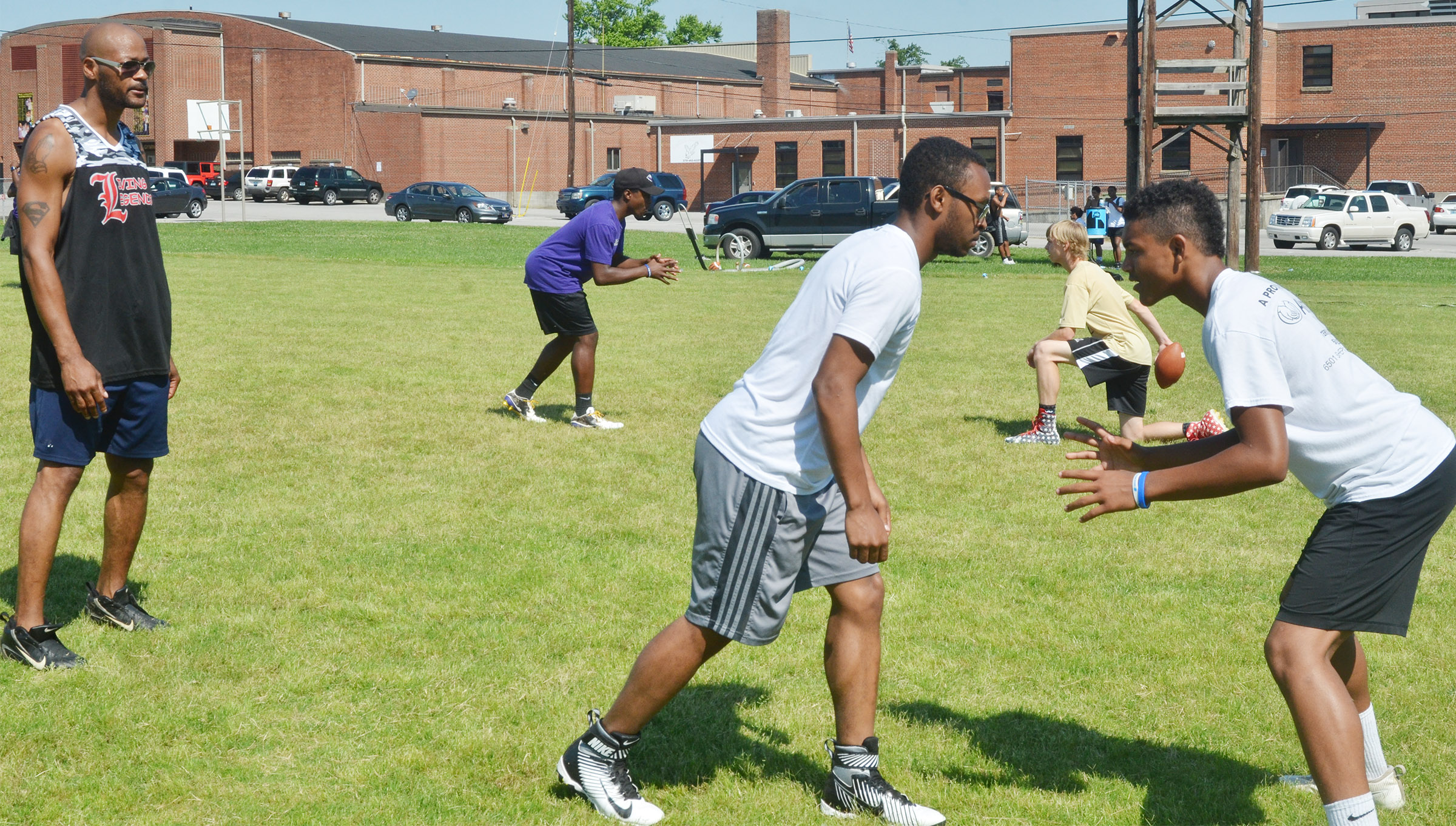 Former NFL player Tony Driver, at left, helps CHS football players as they run a play.