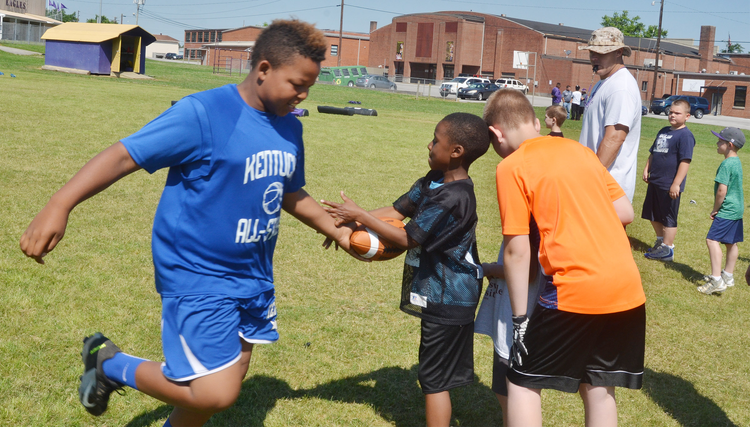 Keondre Weathers passes the ball to John Gholston in the relay race.