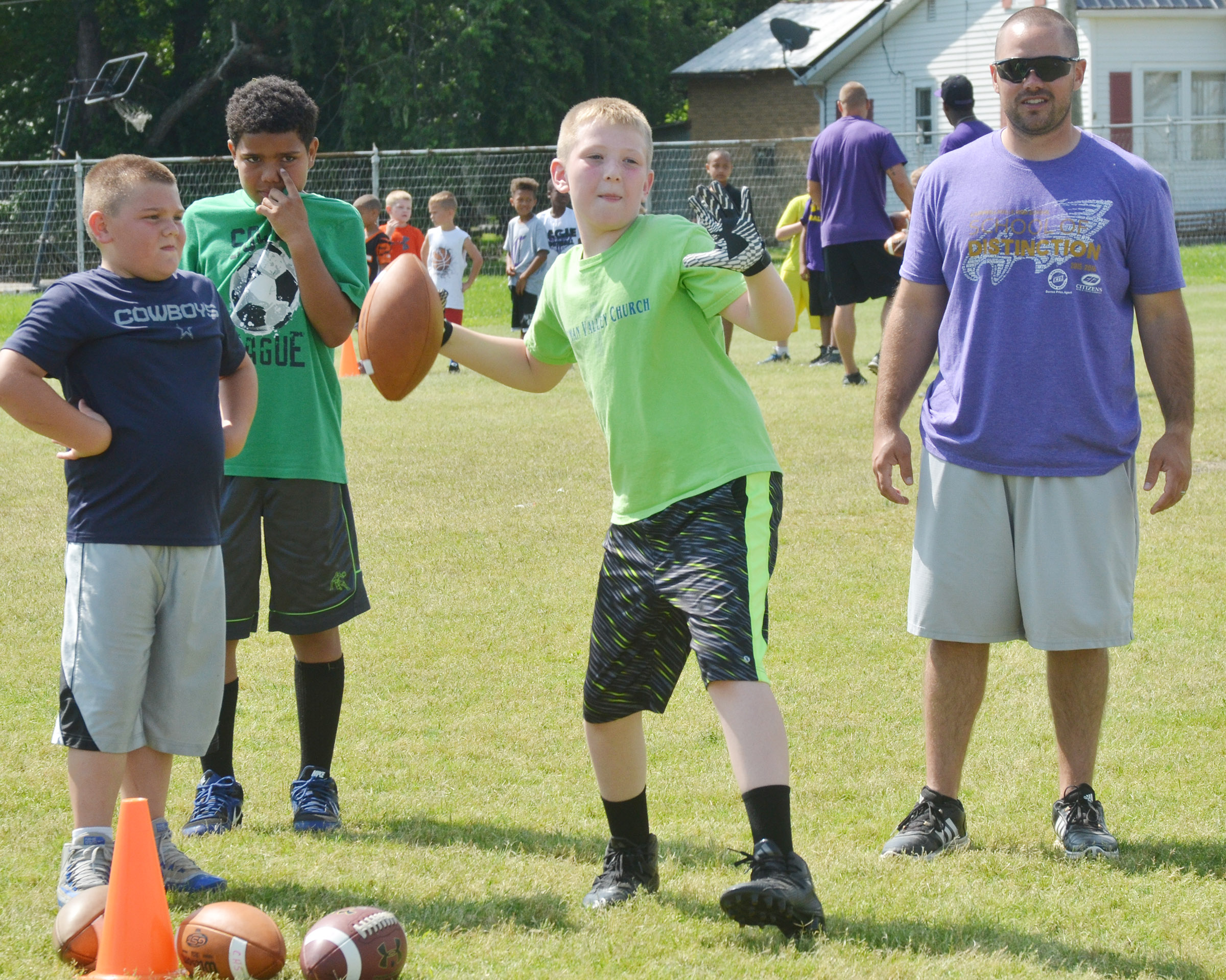 Kaleb Miller throws the ball, with help from assistant coach Blake Milby.