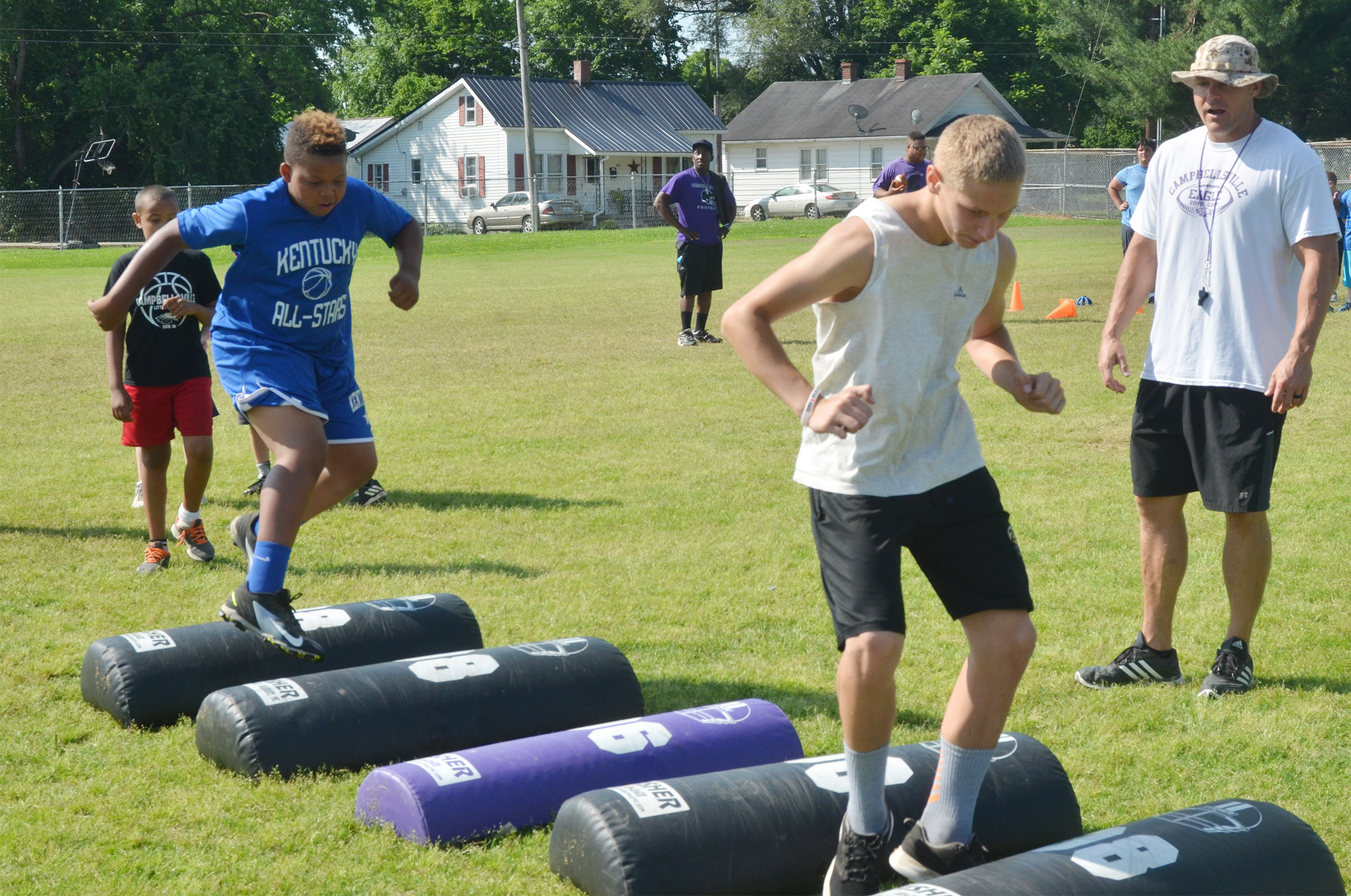 Keondre Weathers, at left, and Damon Johnson work on their footwork with assistant coach Robbie Gribbins.