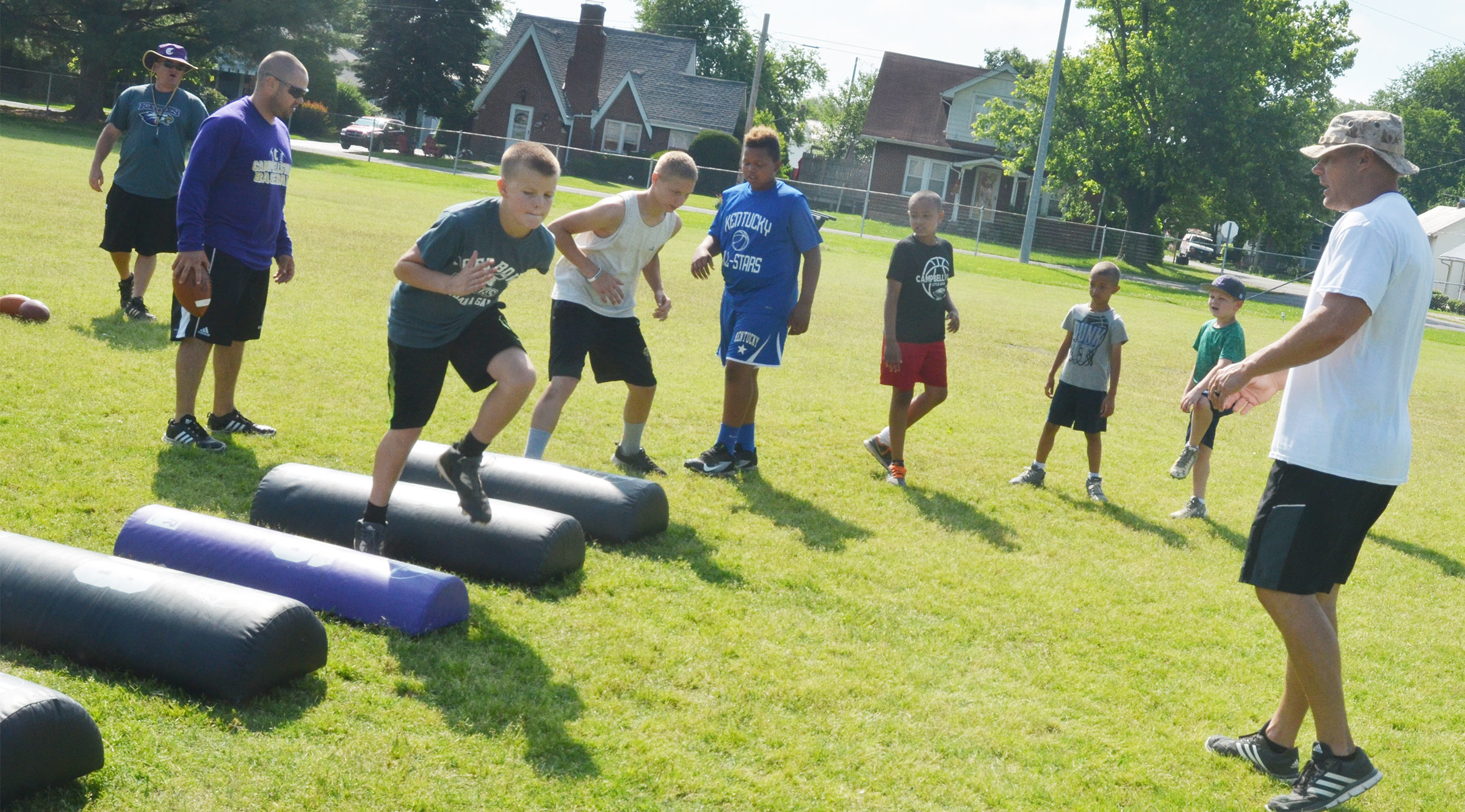 Assistant coaches, from left, Herb Wiseman, Blake Milby and Robbie Gribbins help campers with their footwork.