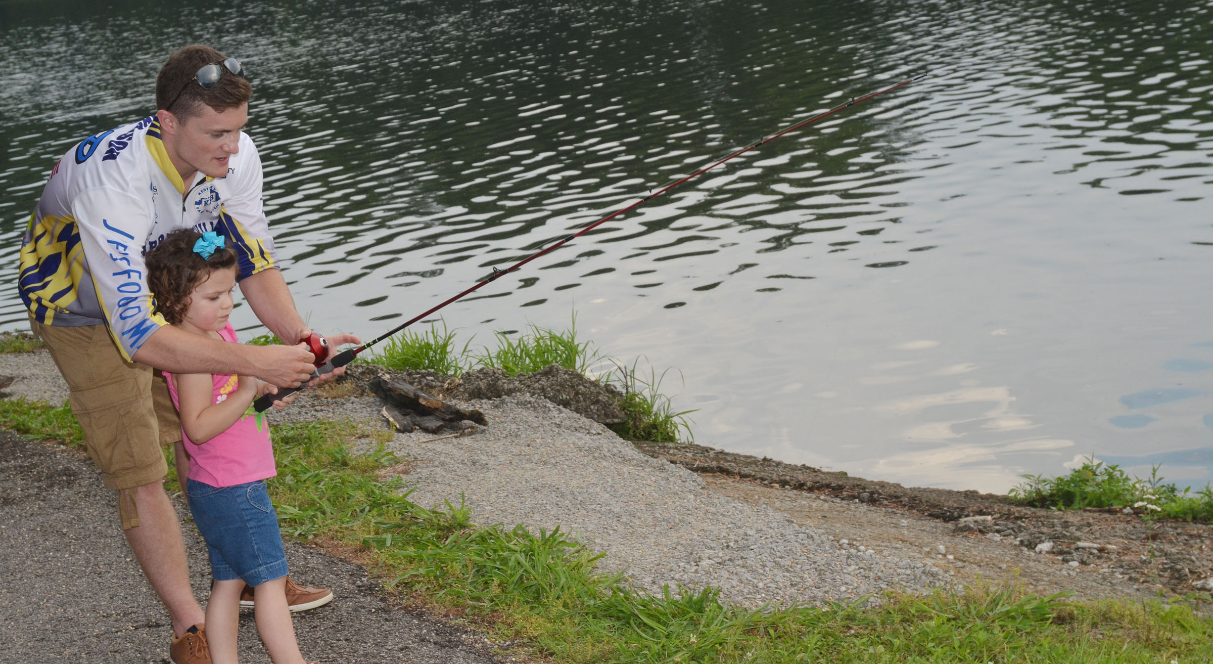 CHS fishing team member Bryce Richardson helps Ava Fields learn to cast.