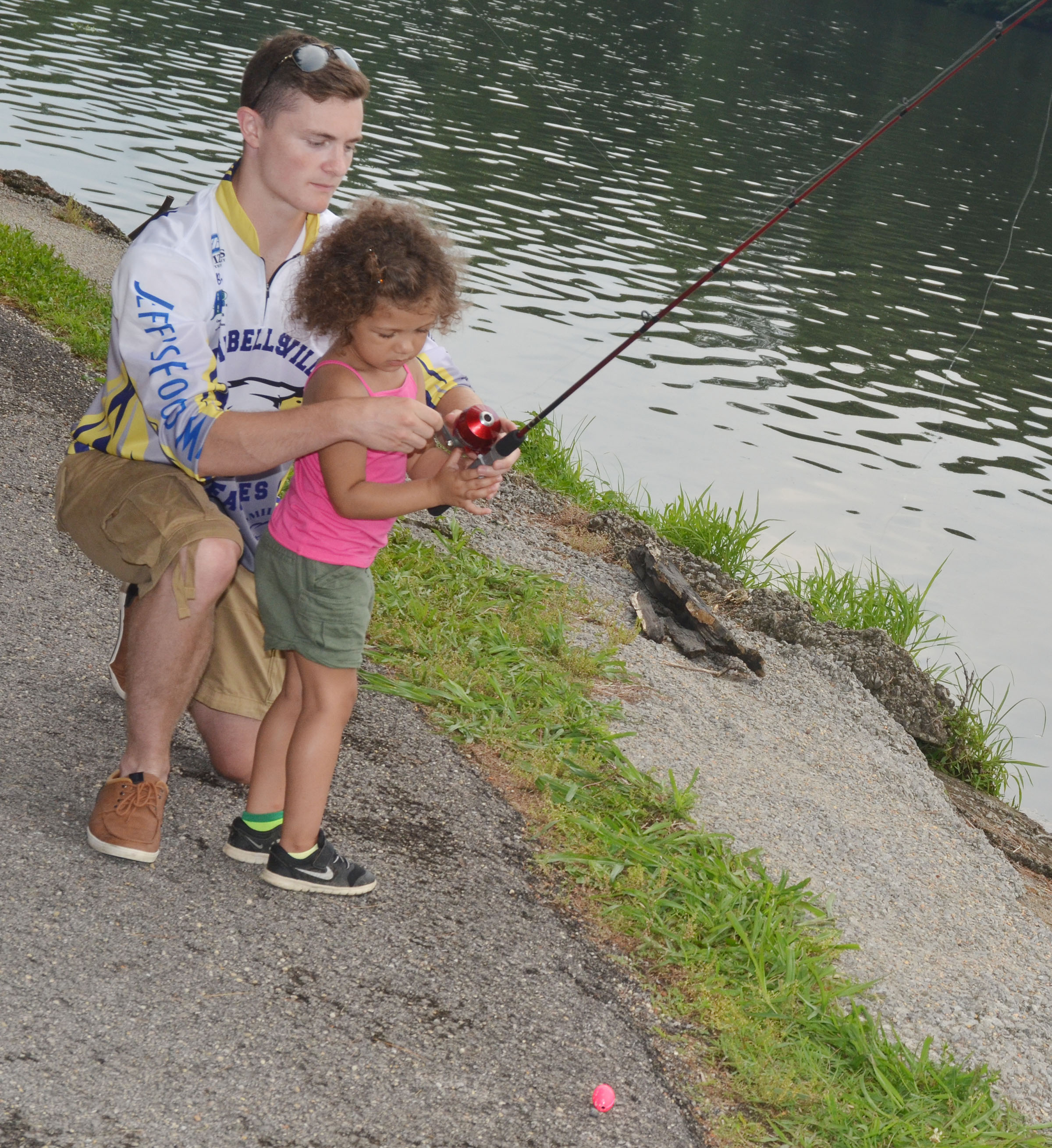 CHS fishing team member Bryce Richardson helps Emilee Coulter learn to cast.