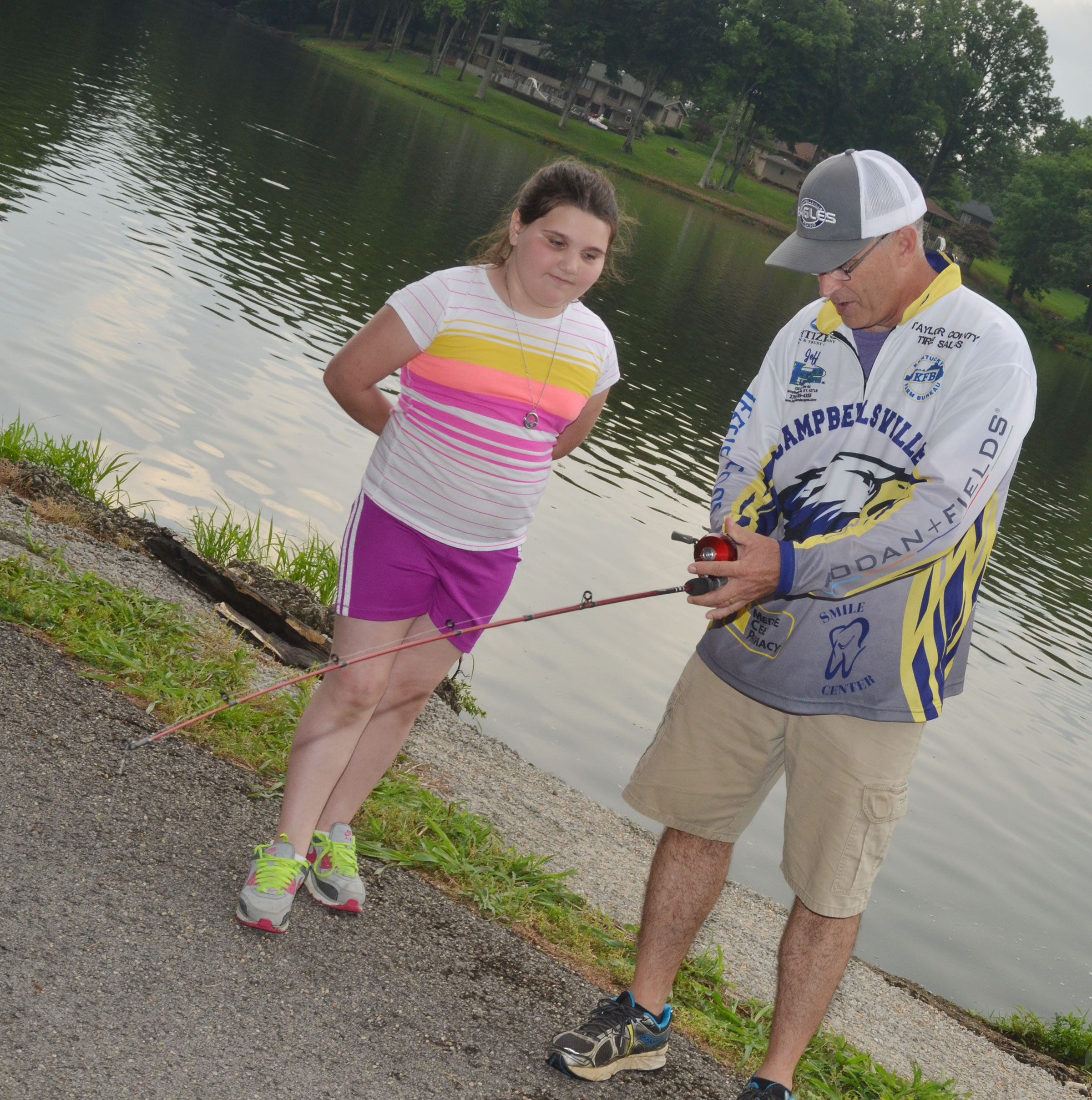 CHS fishing coach Jeff Richardson teaches Campbellsville Elementary School fourth-grader Kailei Hernandez to cast.
