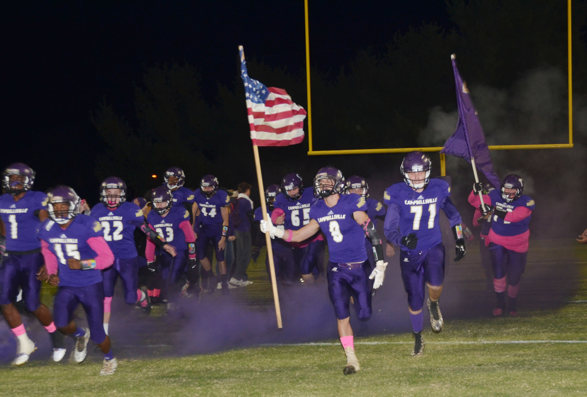 CHS football players take the field in a cloud of purple smoke.
