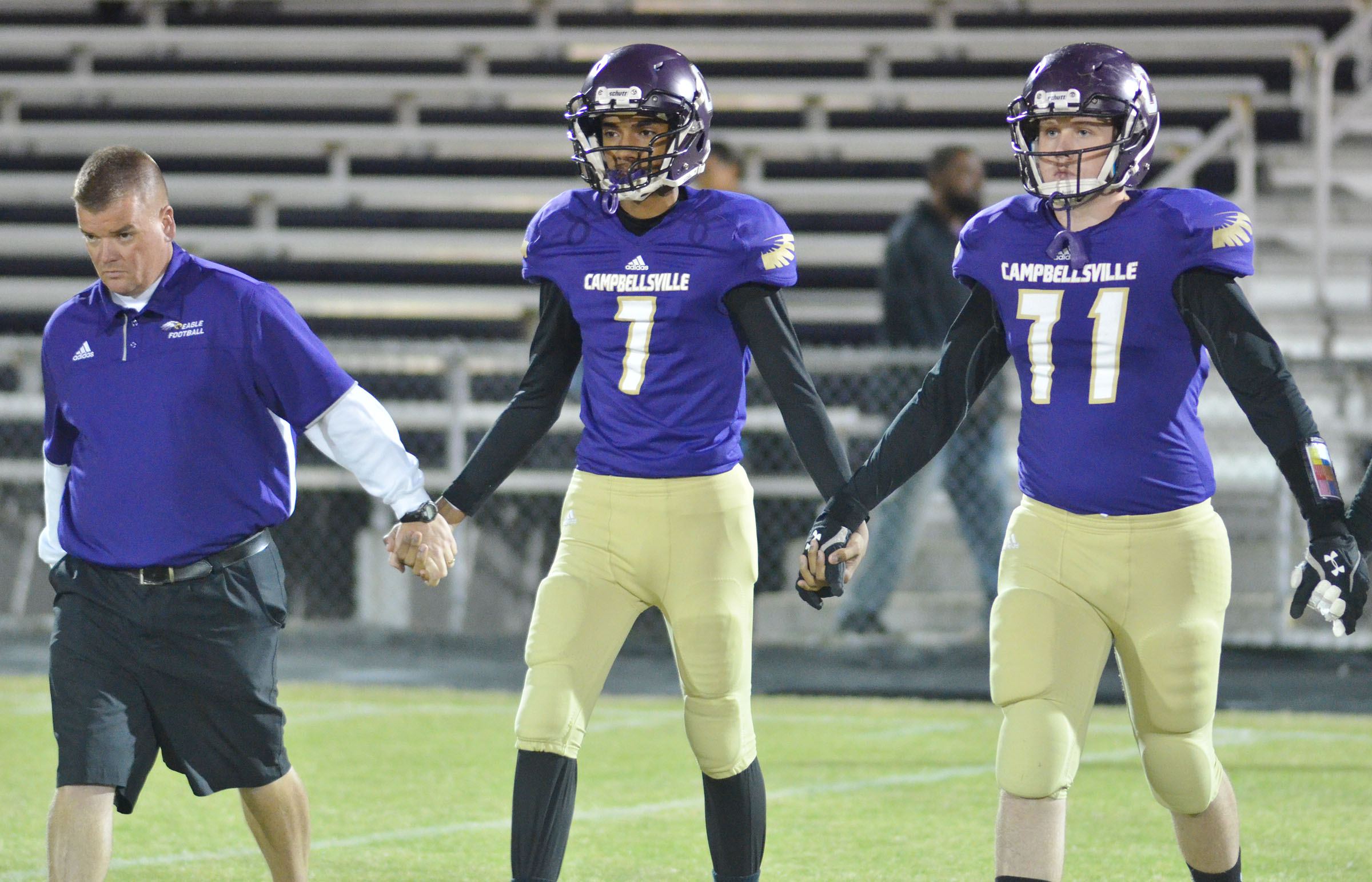 CHS seniors Daniel Silva, at left, and Jared Brewster walk with head coach Dale Estes for the coin toss.