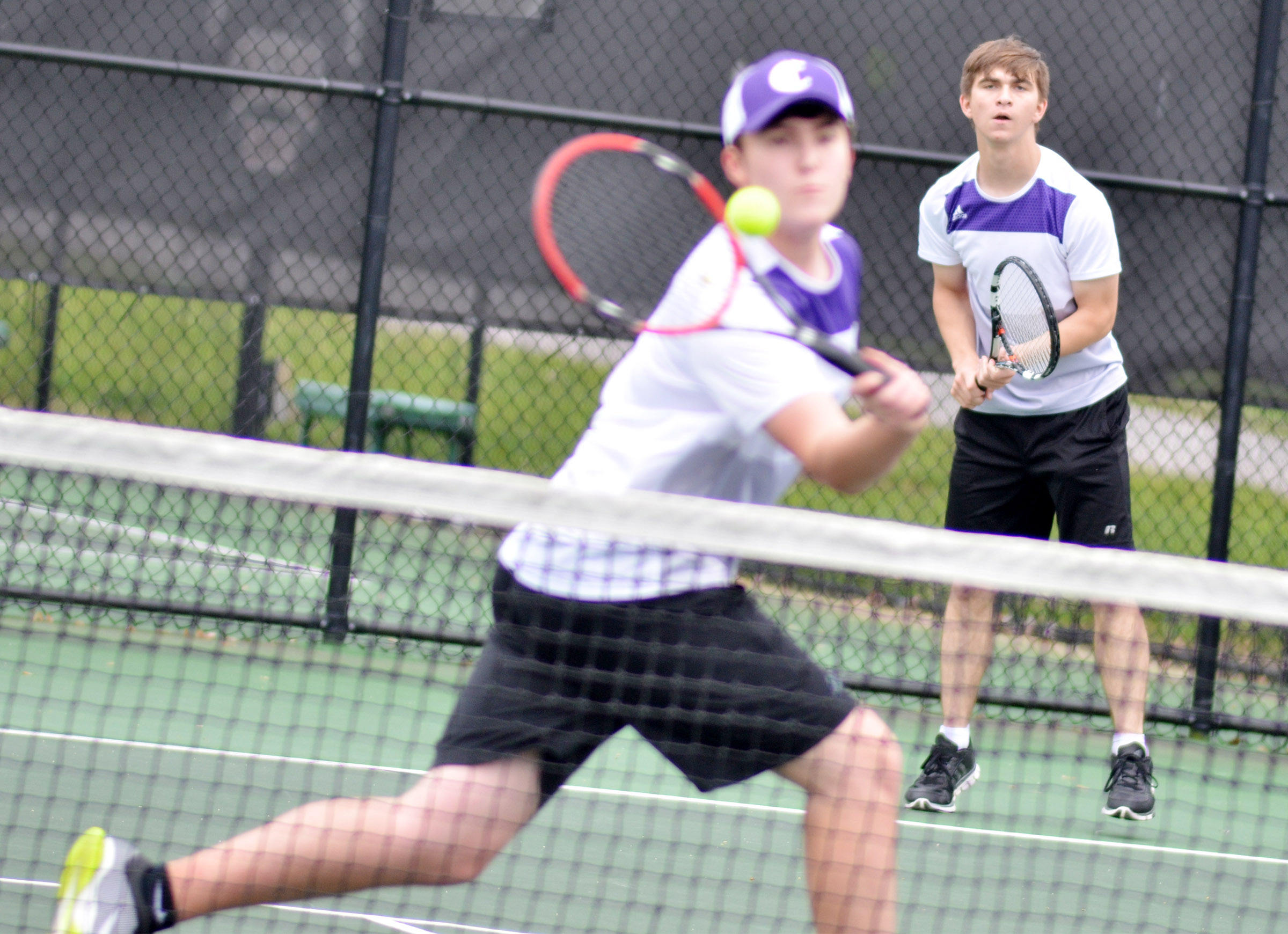 CHS senior Zack Settle hits the ball as doubles partner junior Cass Kidwell watches.