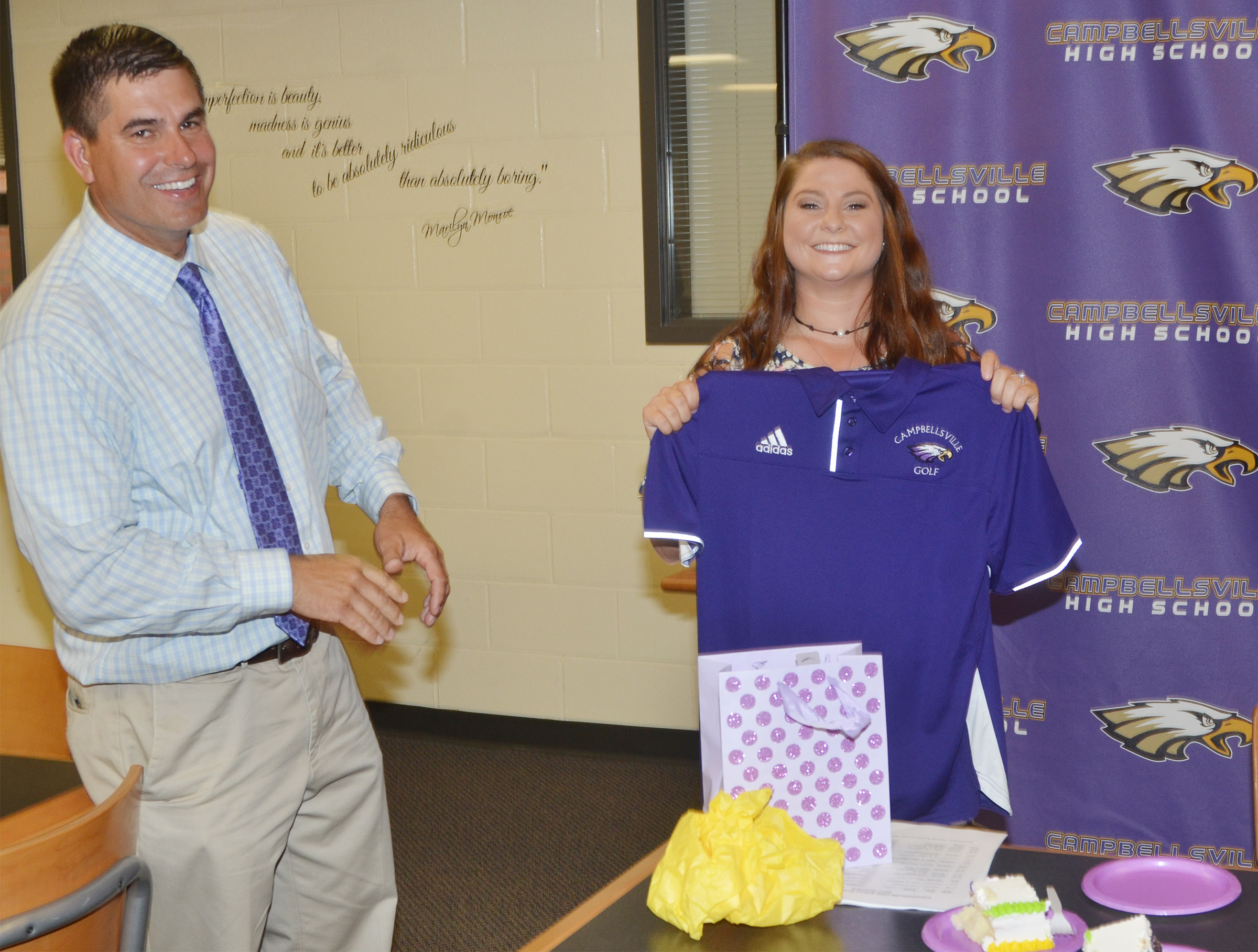 CHS Principal Kirby Smith presents Cassidy Scantland with her first CHS golf shirt.