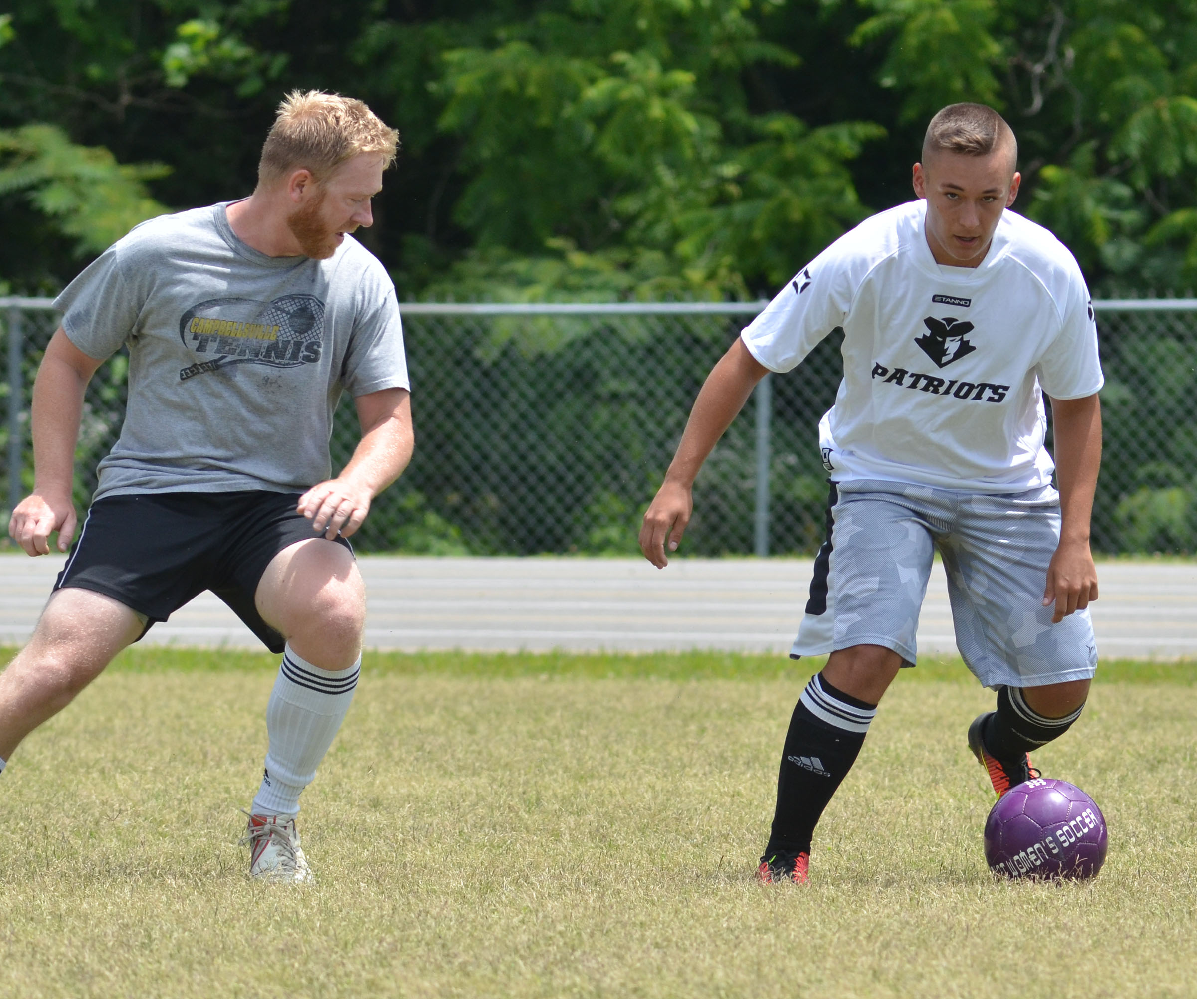 CHS soccer alumni player Luke Lawless battles senior Cody Davis.